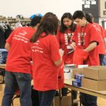 Volunteers stuffing goodie bags for the fair